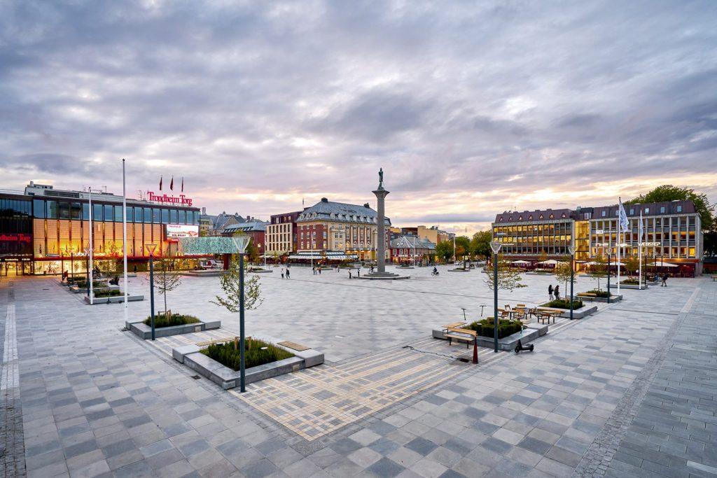 Oversiktsbilde av torvet i Trondheim, med sittegrupper og beplantning. Kjøpesenteret Trondheim Torg på venstre side.